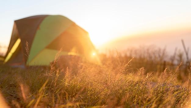 Tenda per vita all'aperto con zaino e sacco a pelo con il paesaggio della natura di estate all'aperto sul tramonto con luce solare luminosa
