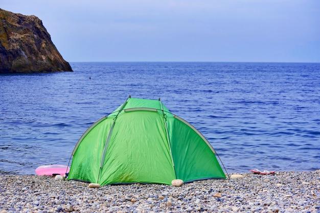Tenda su una spiaggia di ciottoli su uno sfondo di rocce nel mare e cielo.