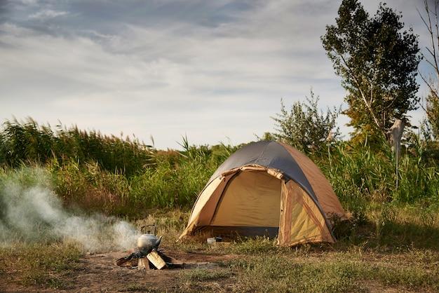 Tenda sulla riva del lago vicino a un fuoco ardente con un bollitore.