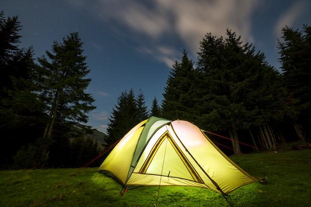 Tenda turistica illuminata su radura verde