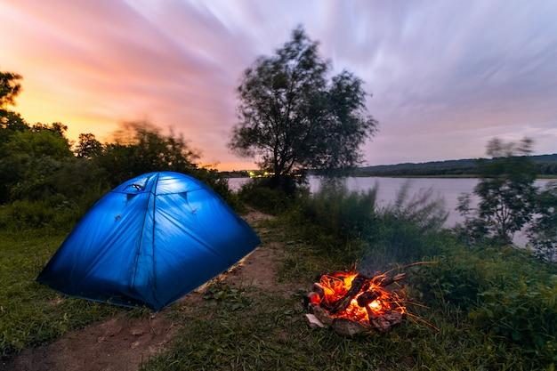 Tenda turistica vicino al fiume. fuoco di accampamento che brucia basso. mattina presto. bel cielo all'alba.