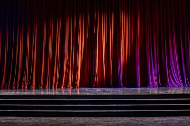 Tende rosse e palco in legno.