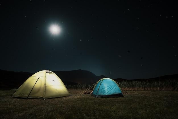 Tende turistiche nell'accampamento fra il prato nelle montagne di notte