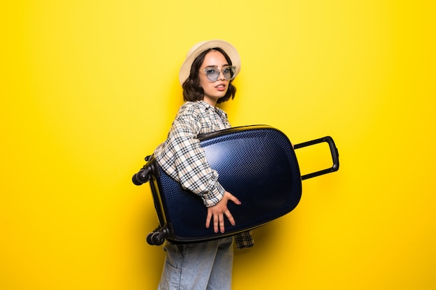 Tendenza giovane donna in occhiali da sole e cappello di paglia pronto per il viaggio estivo isolato