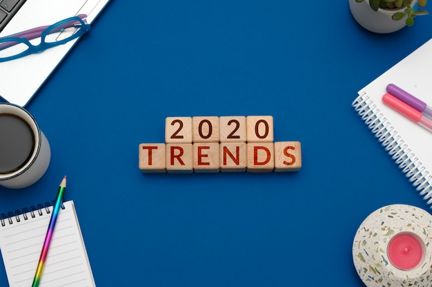 Tendenze 2020. composizione piatta laica con cubi di legno e forniture per ufficio su blu alla moda