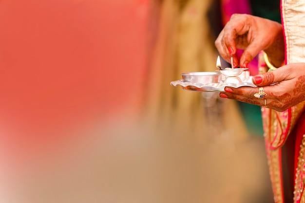 Tenendo in mano la puja thali e la lampada a olio