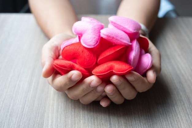 Tenendo la decorazione a forma di cuore rosa e rosso