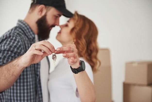 Tenendo le chiavi insieme. coppia felice insieme nella loro nuova casa. concezione del movimento