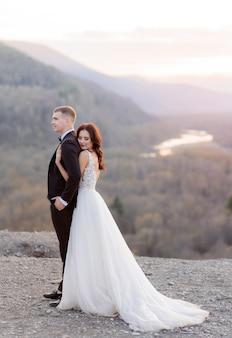 Tenera coppia di sposi sul crepuscolo sulla cima di una collina si abbraccia, vestita in abiti da sposa di lusso