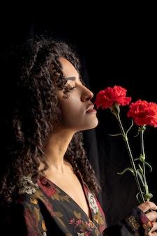 Tenera donna etnica con fiori nelle tenebre