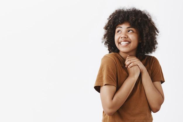 Tenera e sognante carina donna dai capelli ricci dalla pelle scura in maglietta marrone alla moda che si tiene le mani strette sul petto e guarda l'angolo in alto a sinistra con affetto