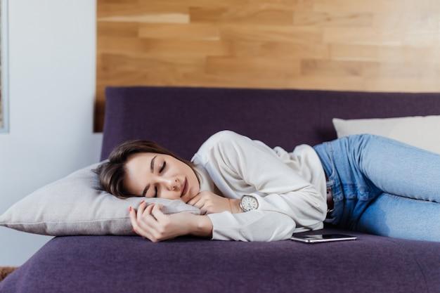Tenera signora sogna sul letto dopo una dura giornata di lavoro