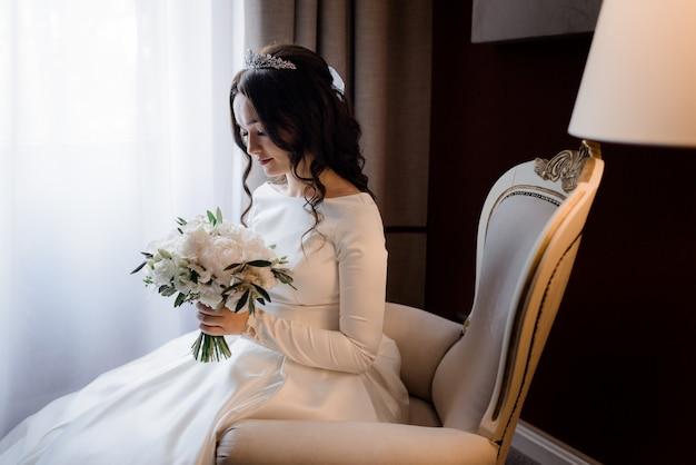 Tenera sposa bruna è seduta sulla poltrona, vestita di diadema e con in mano un bouquet da sposa fatto di eustomas bianchi e peonie