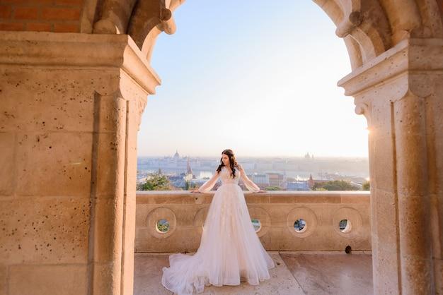 Tenera sposa vestita in abito da sposa alla moda è in piedi sul balcone di un vecchio edificio in pietra