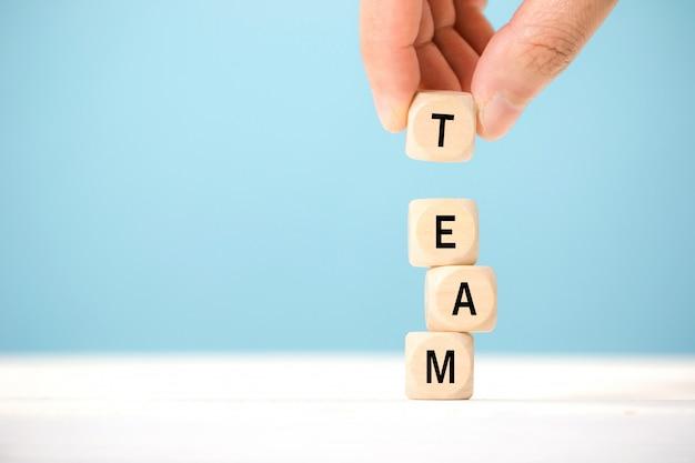 Tenere in mano gli elementi del cubo di legno con la lettera sul tavolo di legno, che rappresenta la squadra. concetto di business