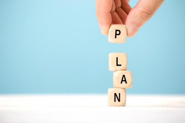 Tenere in mano il cubo di legno con la parola plan. il concetto di pianificazione nel mondo degli affari.