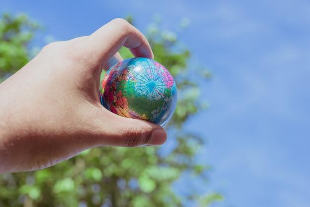 Tenere in mano la plastica del pianeta terra sullo sfondo della natura. salva il concetto del mondo.
