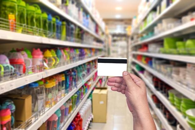 Tenere in mano una carta di credito per acquistare o pagare denaro al supermercato. concetto di tecnologia.