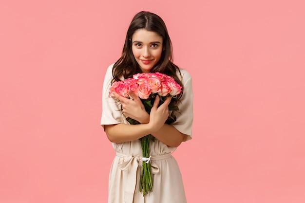 Tenerezza, romanticismo e concetto di amore. femmina attraente del brunette, amica che riceve i bei fiori, abbracciando mazzo e macchina fotografica sorridente contentissima, mostra affetto e felicità, rosa