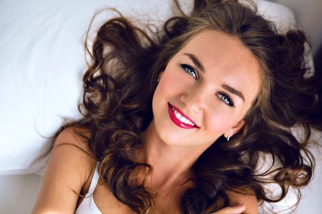 Tenero ritratto di mattina di moda di splendida giovane donna sexy con lentiggini, capelli morbidi e trucco luminoso, sdraiati e rilassati sul letto, viso positivo sorridente carino ed emozioni, colori tenui.