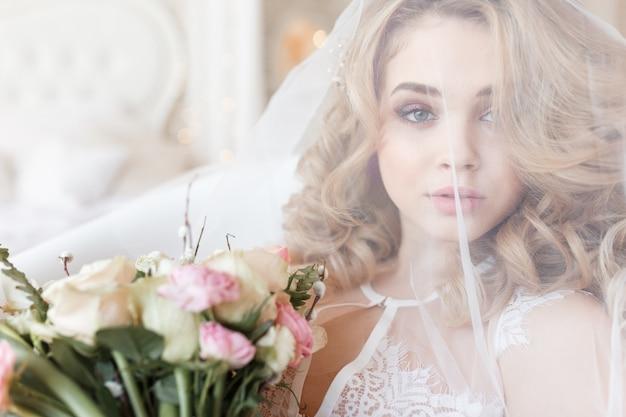 Tenero ritratto di una bella sposa sotto un velo che tiene il mazzo.