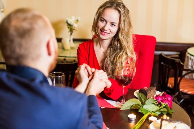 Tenersi per mano della giovane donna dell'uomo al tavolo