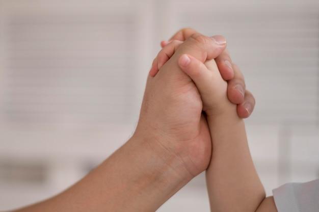 Tenersi per mano della mamma e della figlia