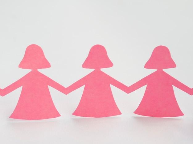 Tenersi per mano della ragazza di carta rosa di disposizione piana