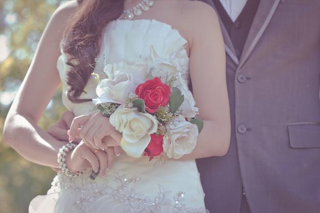 Tenersi per mano dello sposo e della sposa e un mazzo di bei fiori