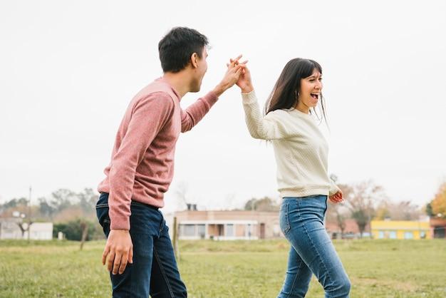 Tenersi per mano di camminata delle giovani coppie allegre