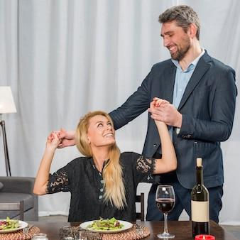 Tenersi per mano felice dell'uomo di donna allegra al tavolo