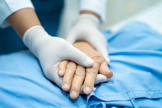 Tenersi per mano paziente senior asiatico della donna con amore.