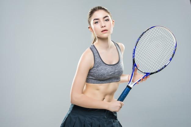 Tennis bello della ragazza con una racchetta sulla parete bianca isolata. annuncio di tennis.