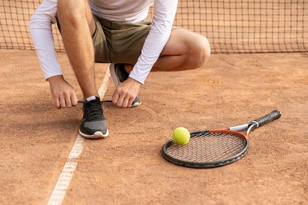 Tennis che lega le sue scarpe
