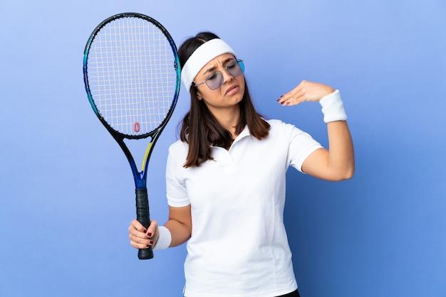 Tennis della giovane donna sopra isolato con l'espressione stanca e malata