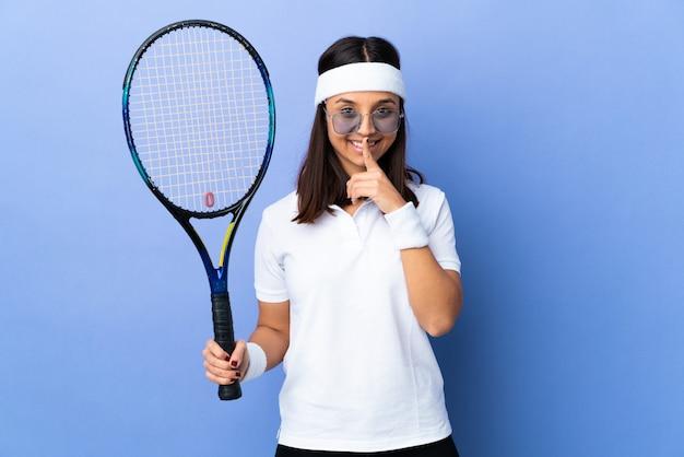 Tennis della giovane donna sopra la parete che mostra un segno di gesto di silenzio che mette dito in bocca