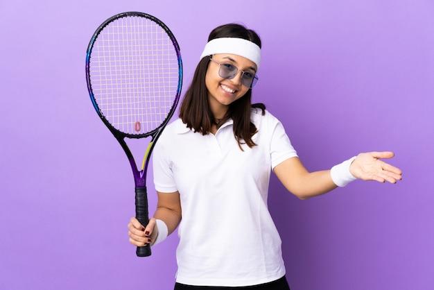 Tennis della giovane donna sopra la parete che presenta e che invita a venire con la mano