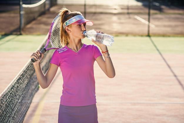 Tennis femminile in acqua potabile dell'uniforme rosa dalla bottiglia di plastica dopo l'addestramento di tennis sulla corte all'aperto al tramonto.