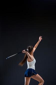 Tennista bella ragazza con una racchetta su sfondo scuro