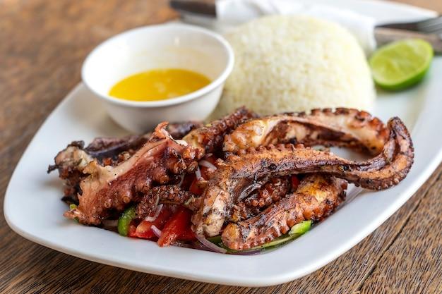 Tentacoli fritti del polipo con riso bianco su un piatto, fine su