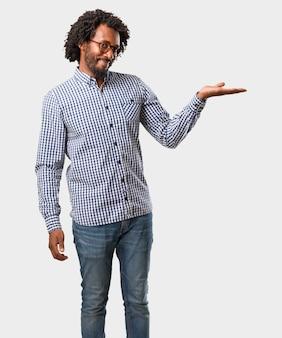 Tenuta afroamericana bella dell'uomo di affari qualcosa con le mani, mostranti un prodotto, sorridente e allegro, offrendo un oggetto immaginario