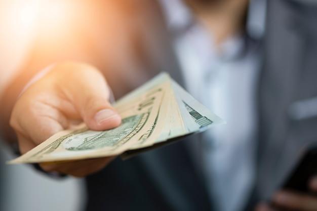 Tenuta dell'uomo d'affari che dà le banconote del dollaro