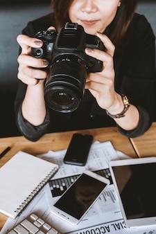 Tenuta della donna del primo piano con la macchina fotografica di fotografia