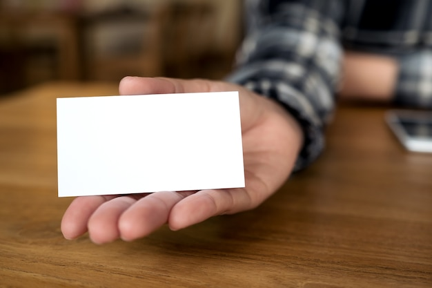 Tenuta della donna di affari, mostrando e dando un biglietto da visita sulla tavola di legno