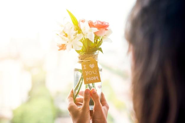 Tenuta della donna in vaso delle mani dei fiori per il giorno del `s della madre
