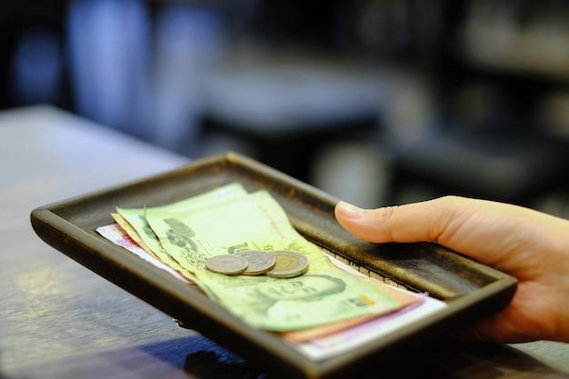 Tenuta della mano del primo piano di bill con la banconota e le monete tailandesi dei soldi