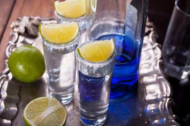 Tequila sparato con calce e sale marino e bottiglia blu sul vassoio