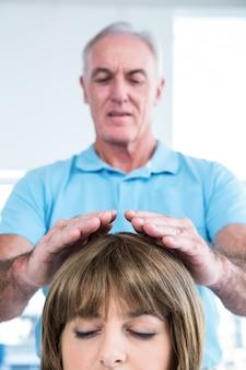 Terapeuta maschio che esegue reiki sopra la donna