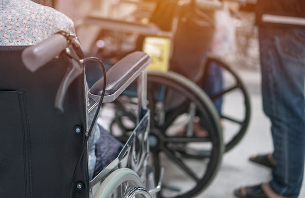 Terapia di servizi di attesa di sedia a rotelle di seduta paziente paziente disabile dell'uomo anziano da medico nella clinica dell'ospedale