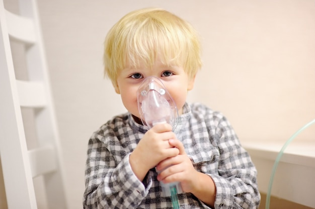 Terapia inalatoria del ragazzo sveglio dalla maschera dell'inalatore. chiuda sull'immagine di un bambino con problema respiratorio o asma. ragazzo malato con maschera trasparente all'ossigeno.